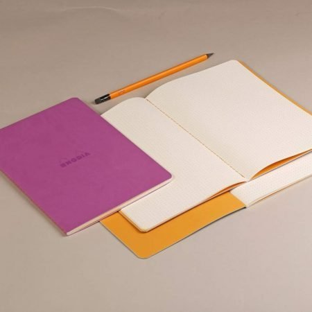 Rhodia Rhodiarama Sewn Spine Notebooks, show open on a grey surface.