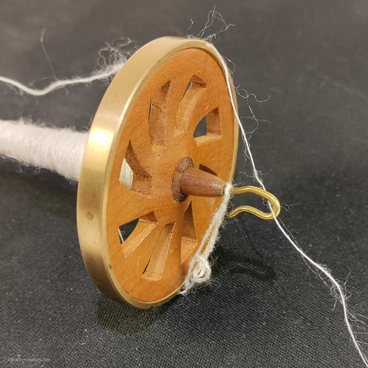 closeup of a spindle with chain ply on the fly and some single. there is some fuzz around the yarn.