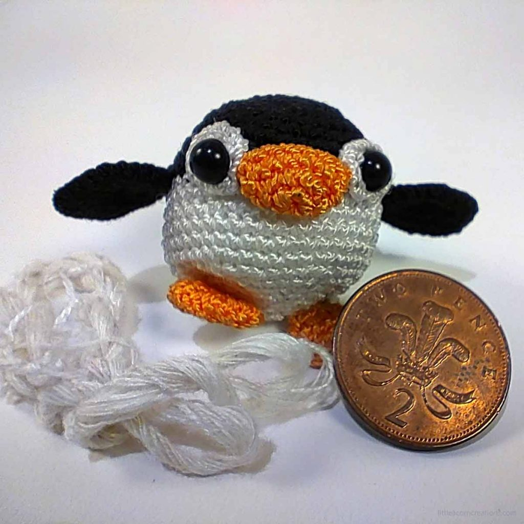 16 yards of chain plied silk in front of a 2 pence coin and a small amigurumi crocheted penguin for scale