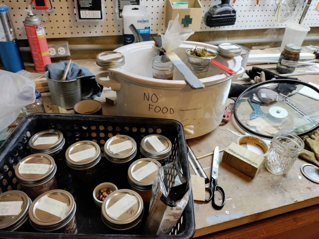 straining the dye liquids into new jars on a messy workbench.
