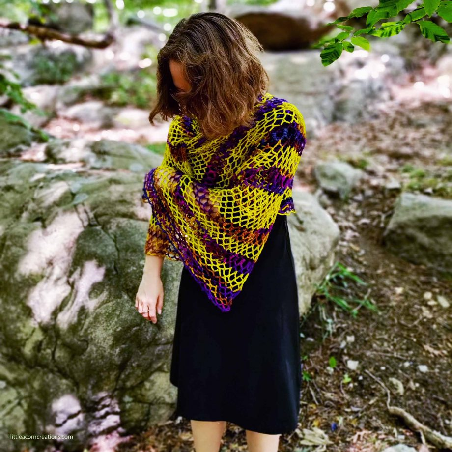 """Northern Lights Crochet Wrap, drape detail, shown on 5'2"""" model in an outdoor setting."""