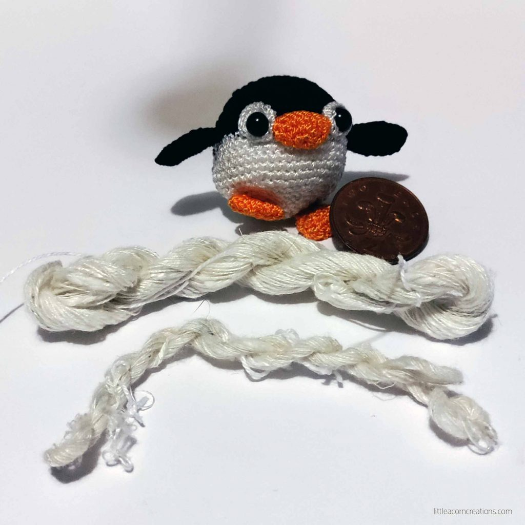 small amigurumi penguin, two pence coin, and two small skeins on handspin silk