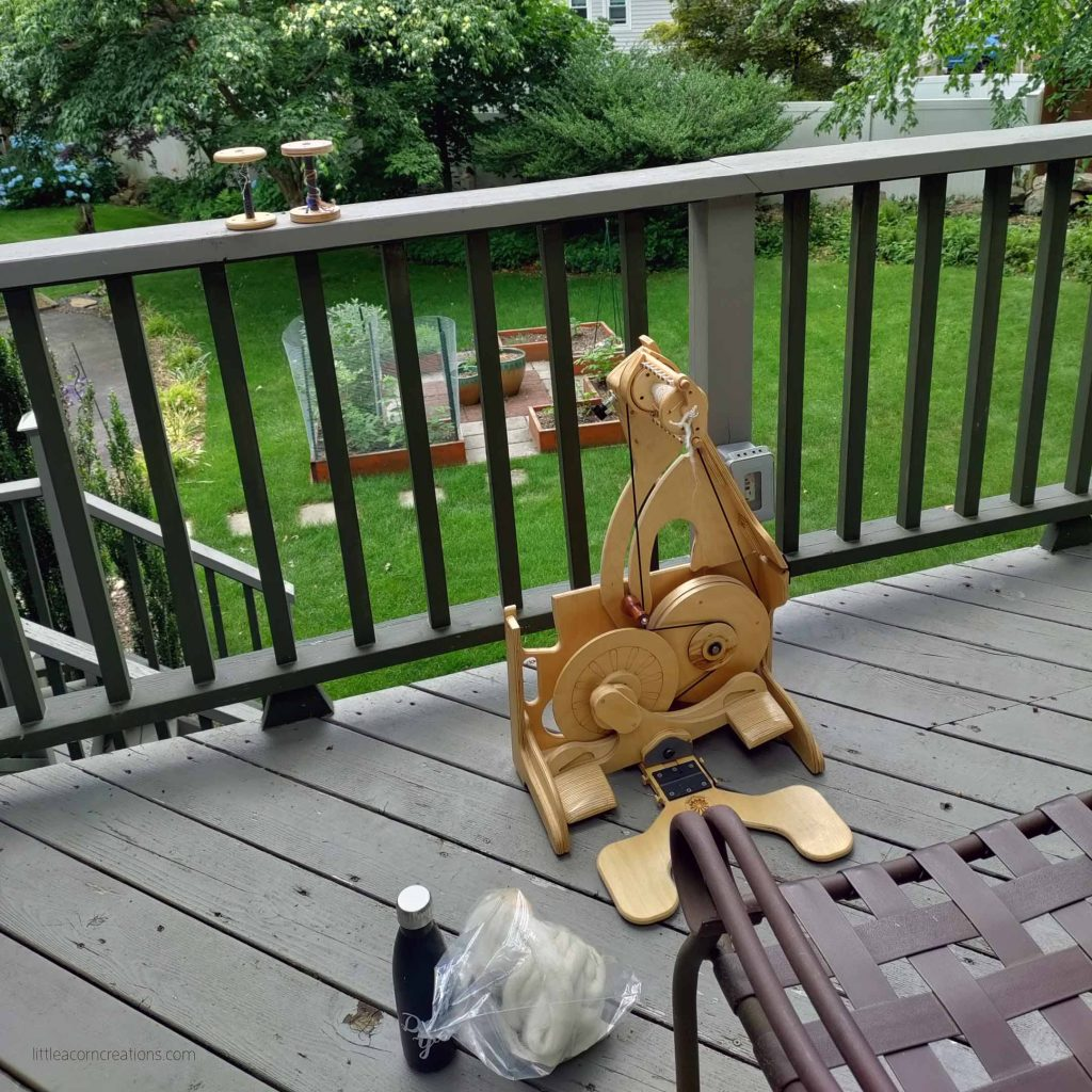 spinolution bee spinning wheel on a deck with view to backyard. there are two empty bobbins on the railing
