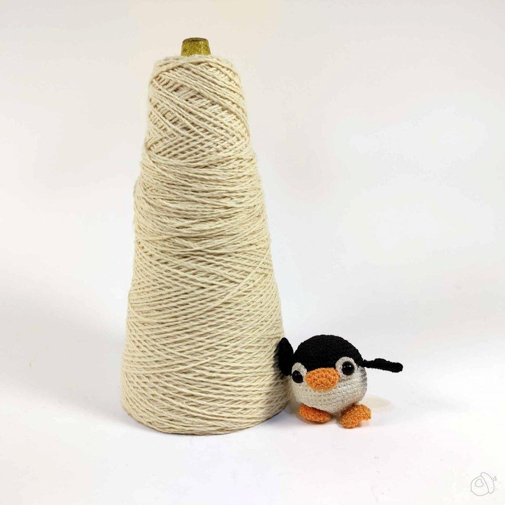 cone of yarn and small amigurumi penguin