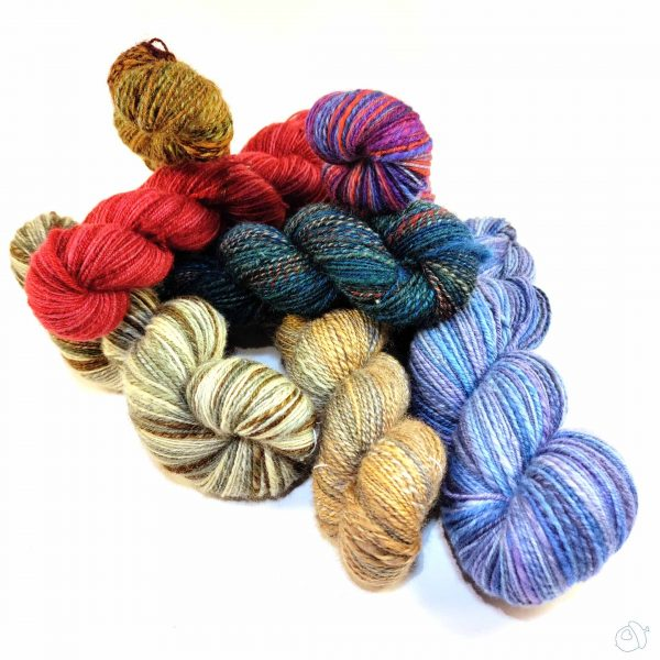 pile of handspun skeins on a whiite background