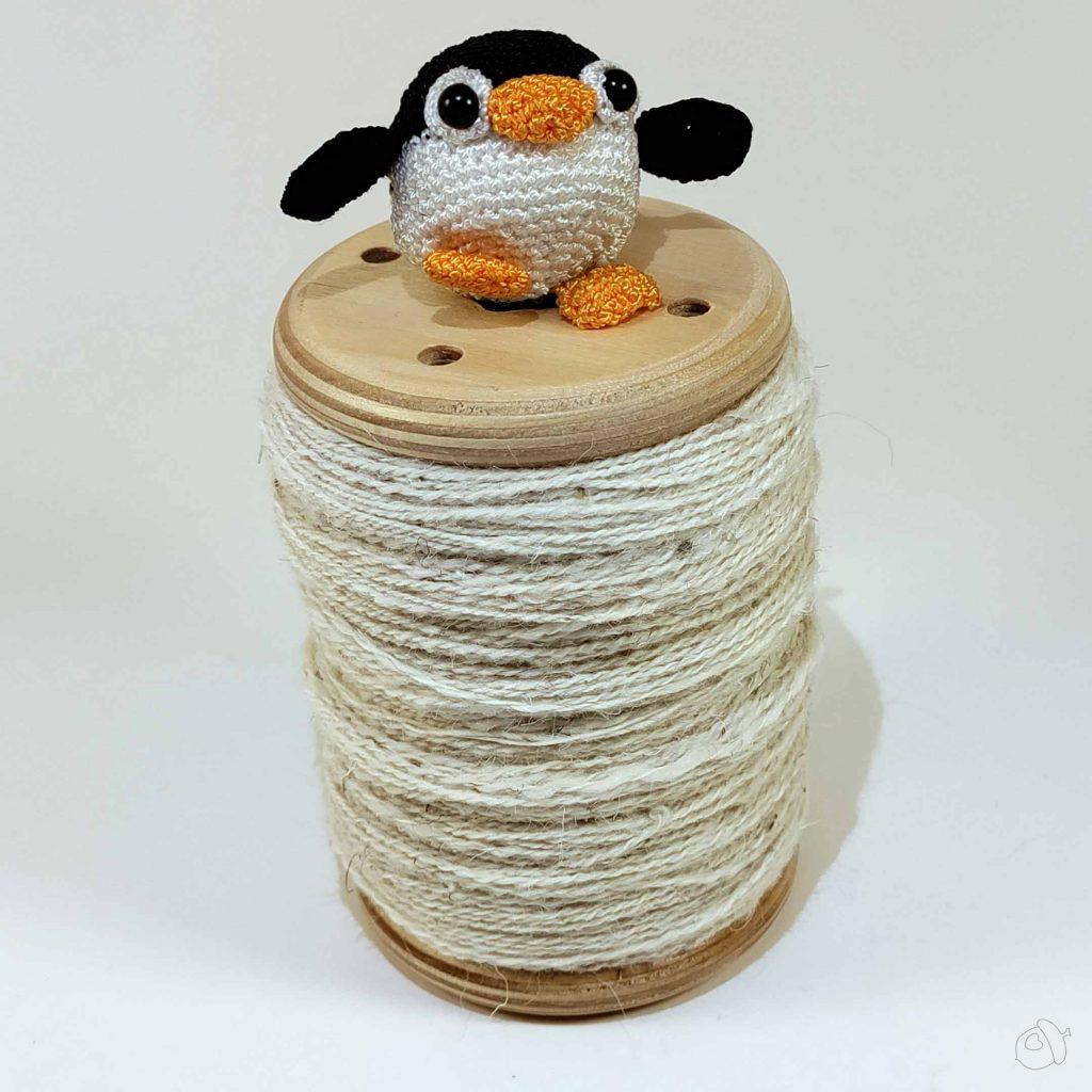 small amigurumi penguin atop a full bobbin of churro