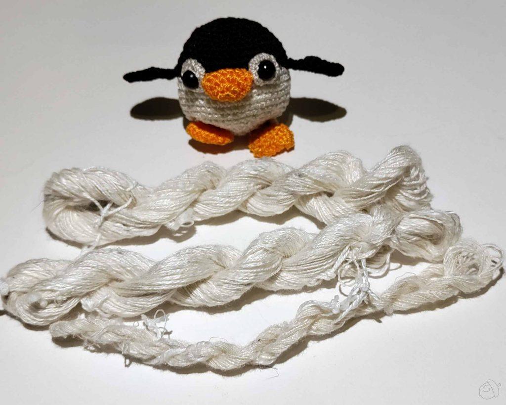small amigurumi penguin with three skeins of silk