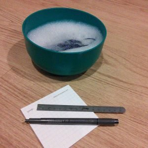 """a plastic bowl with sudsy water and some knitting. a post it with """"gauge"""" handwritten, a pen, and a small ruler is in front of the bowl"""