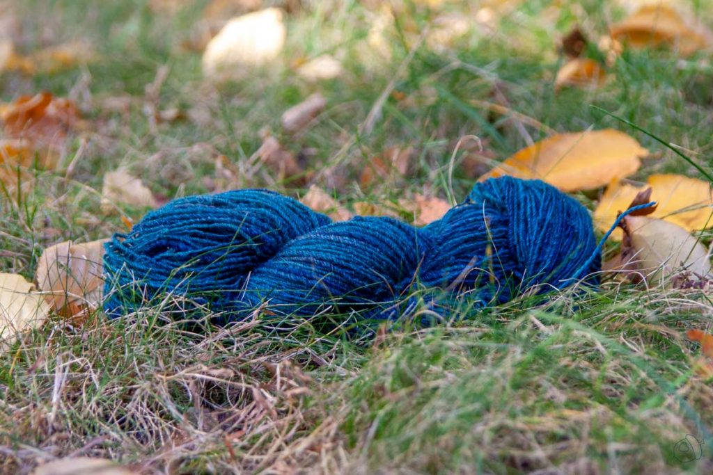 Skein of dark teal handspun laying on a grass lawn