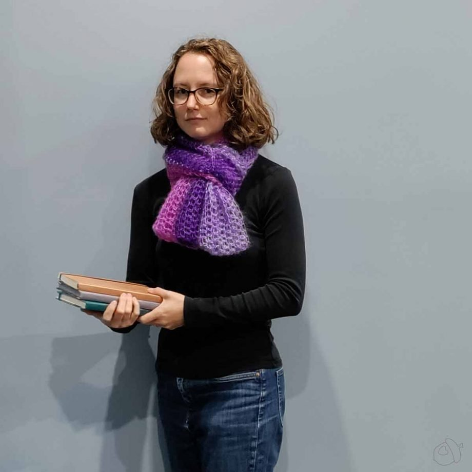 Cirrostratus Cowl, worn looped as a small scarf. The model is holding some notebooks.