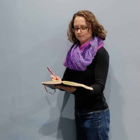 Cirrostratus Cowl, worn doubled. The light purple is prominent. The model is writing in a notebook.