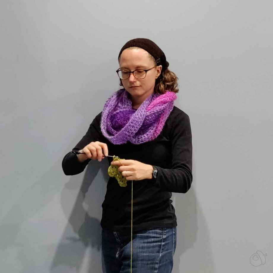 Cirrostratus Cowl, worn doubled. The model is crocheting green yarn