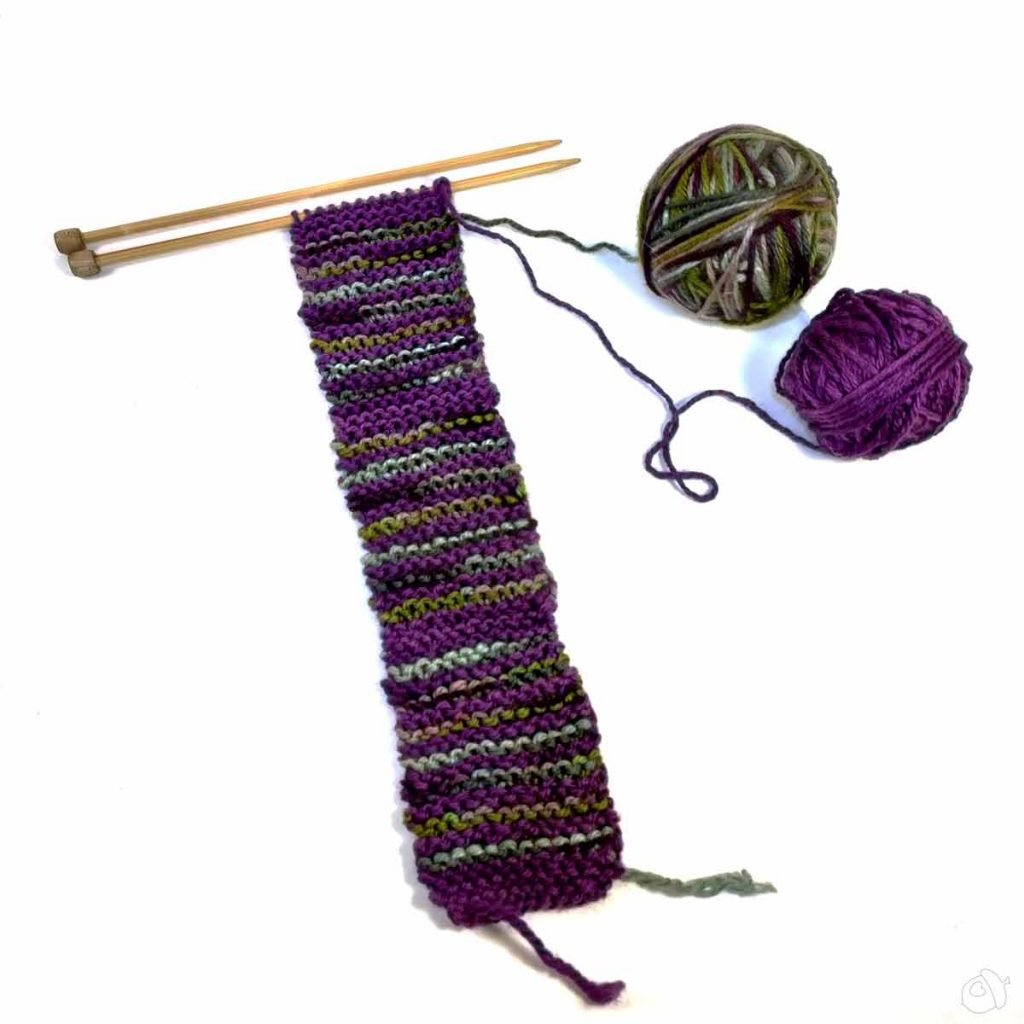 knit striped swatch, in purple anda varigated purple-green-grey yarn. The striped sections are seperated by solid purple knitting.