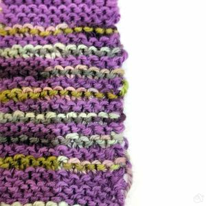 inconsistent knit striped swatch, in purple anda varigated purple-green-grey yarn. This swatch shows additional inconsistencies in changing the working yarn.